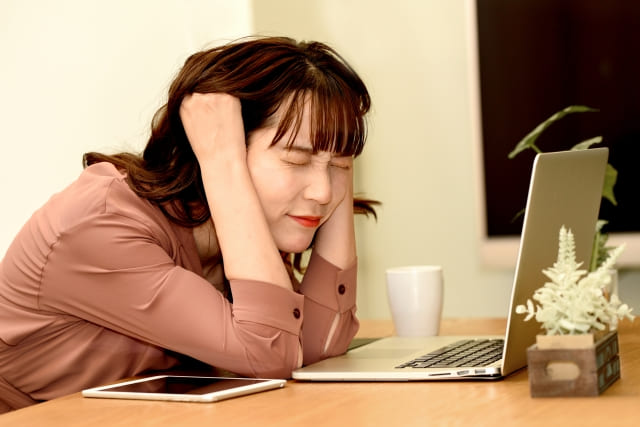 PCの前で頭を抱える女性
