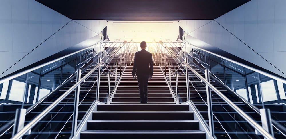駅の階段を登る男性